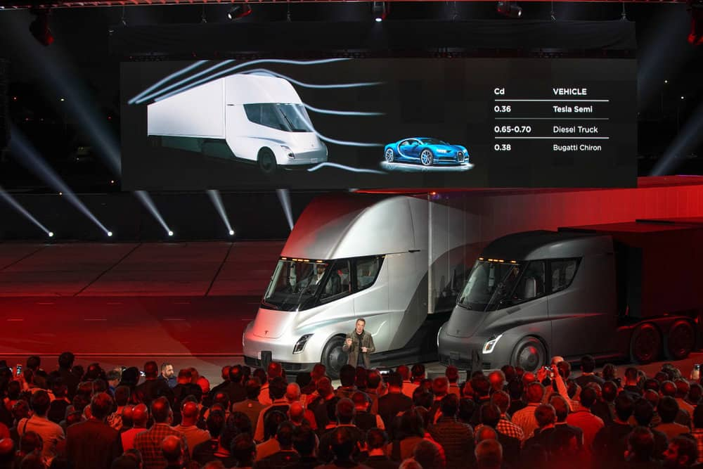 Elon Musk stands in front of two Tesla Semi models during a grand unveiling in 2017.