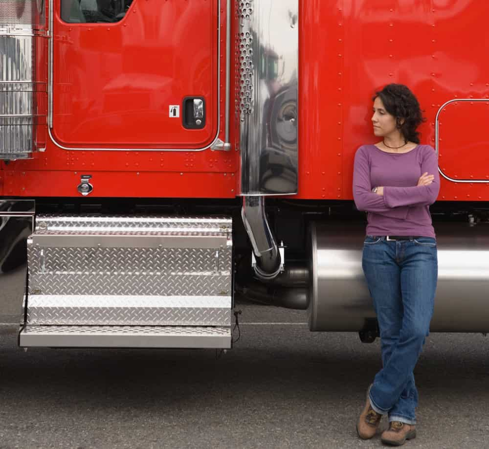 A driver stands near the cab of her truck.