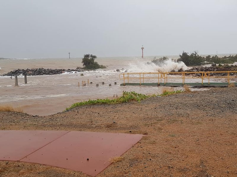 In this EXCLUSIVE photo  , we can see what a spring tide-storm surge tide looks like at Port Hedland. This is a marine launch jetty (the dark greenish platform with a yellow guard rail). Readers can observe the wooden stumps just above the water to its immediate left. And, to the far left, there are a couple of logs sticking out of the water. That is the marine jetty. The water level is supposed   to be below   that jetty by a couple of feet. Mariners normally jump up from the side of the launch onto the jetty. Photo: supplied to FreightWaves by a source.