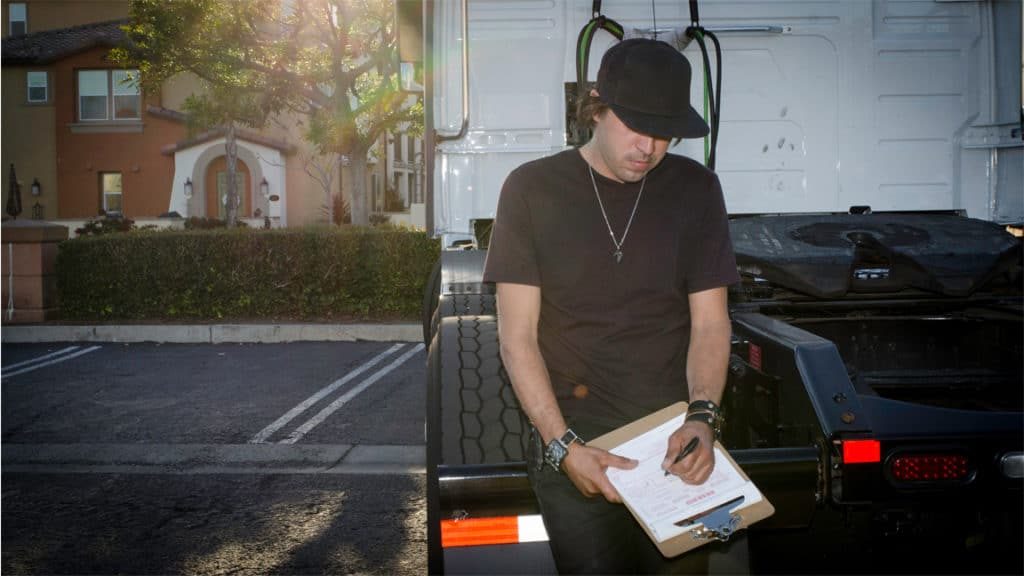 Truck driver filling out paperwork outside his rig. (Photo credit: Jim Allen/FreightWaves)