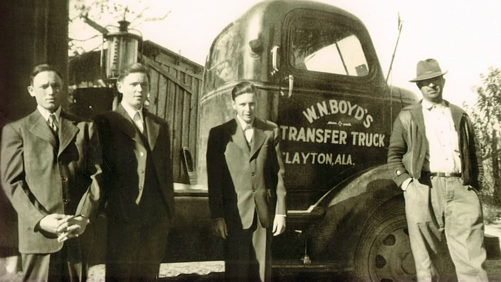 image courtesy of Flickr/Trucking PR   Cecil Boyd, at left, and his brothers Hilly and Dempsey, stand next to a tractor their father, William Boyd, right, operated. Following World War II, the Boyd brothers drove trucks for 10 years before starting their own company in 1956 - Boyd Brothers trucking.