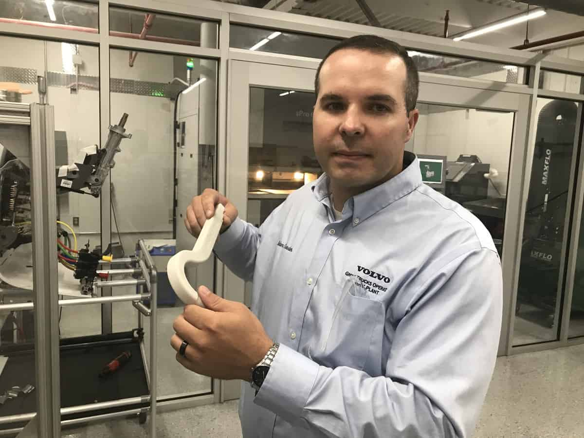 Adam Crowder holds a 3D-printed hook that Volvo Trucks uses to open truck doors before painting.