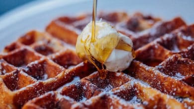 Closeup of maple syrup pouring onto butter and waffle