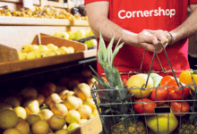 Cornershop worker holds basket of fresh fruits and vegetables in the produce section of a grocery store.