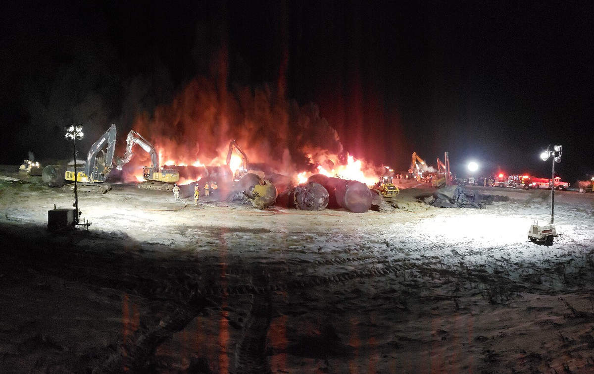 A photograph of fire burning next to some tank railcars. The photo was taken at night.