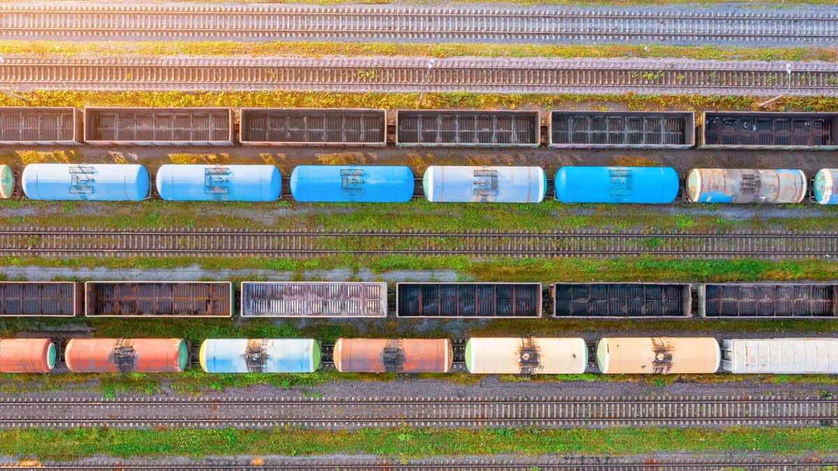A photograph showing two rows of tank cars and two rows of empty railcars.
