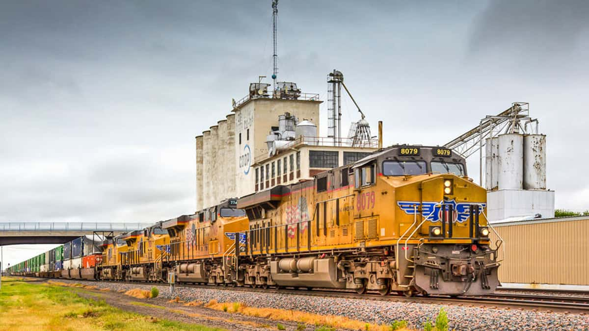 A photograph of a train in front of a grain elevator.