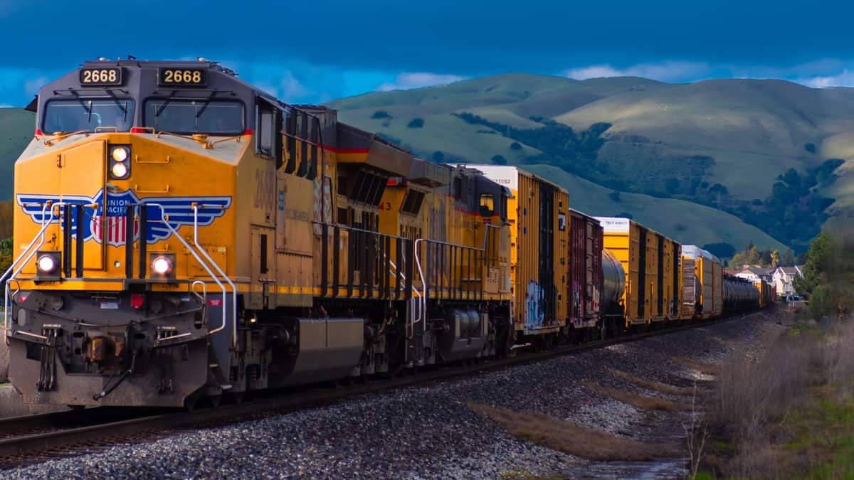 A train travels on train tracks. Behind the train are mountains.