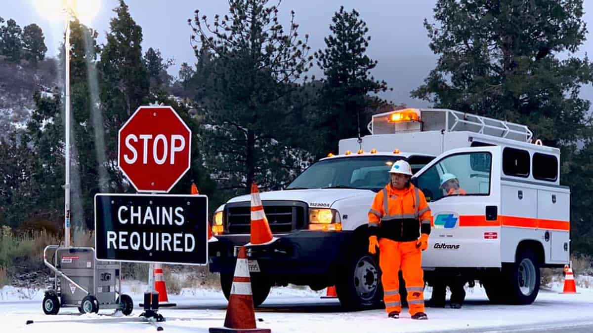 """Road crew in southern California mountains posting """"Road Closed"""" sign."""