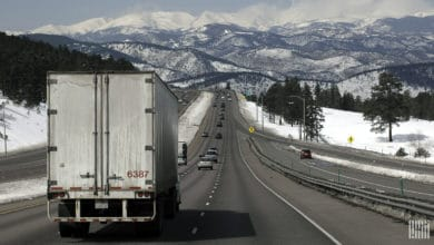 Tractor-trailer on I-70 in Colorado, surrounded by snow-covered mountains and grass.