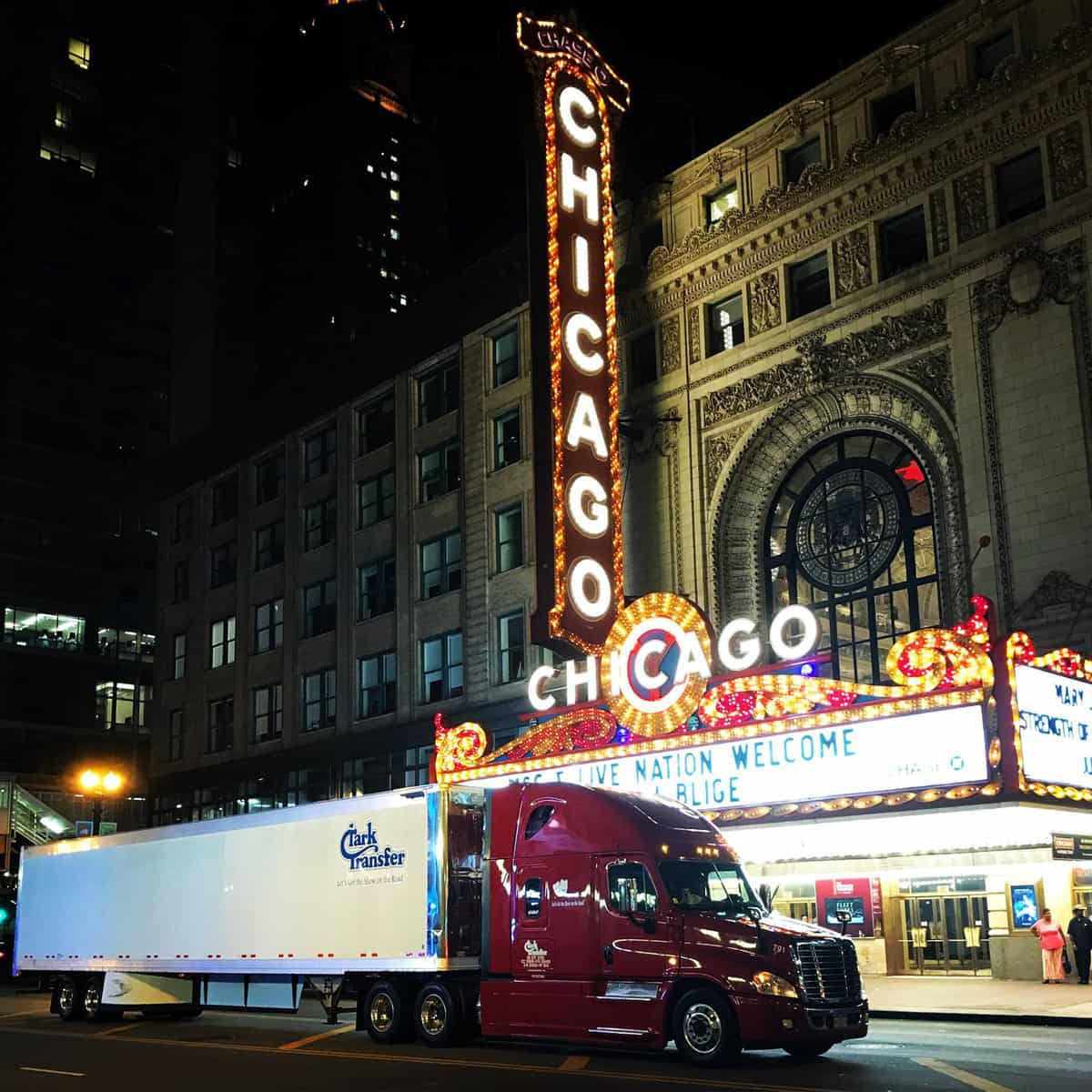 A photograph of a truck and trailer at night. The truck is in front of a brightly-lit theater with a neon marquis.