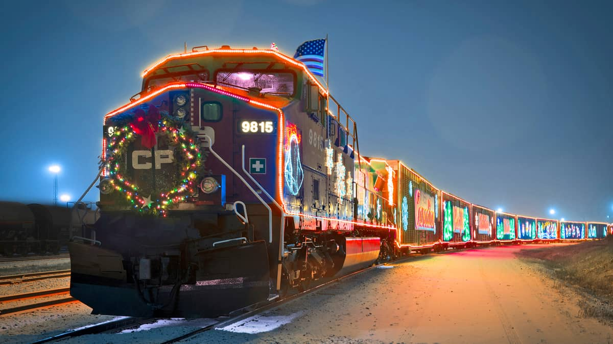 A photograph of a train at night. The train is decorated with Christmas lights and holiday decorations.