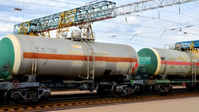 Two tank cars sit in a railroad yard.