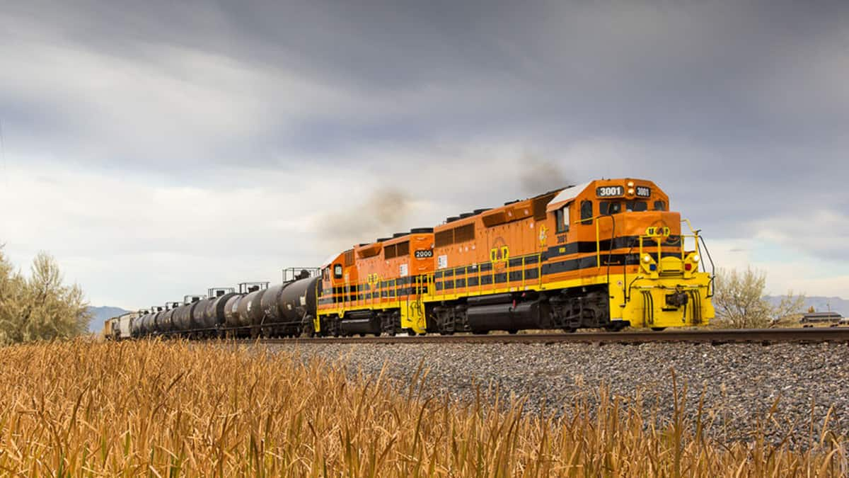 A photograph of a locomotive pulling tank cars across a field.