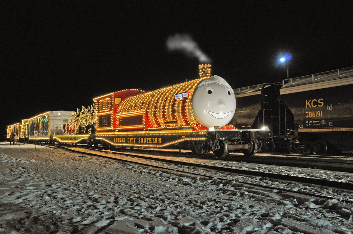 A photograph of a locomotive and railcars decorated with hundreds of holiday lights. The face of a Thomas the Train, a cartoon character, is attached to the front of a locomotive.