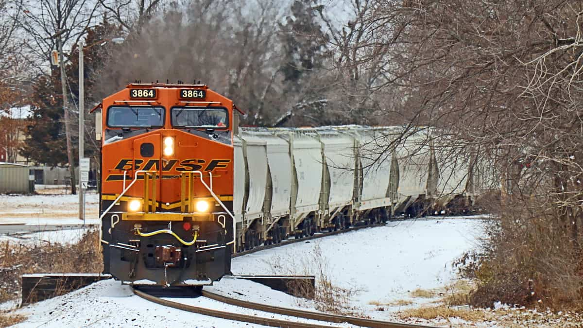 A photograph of a train passing through patches of snowy ground.