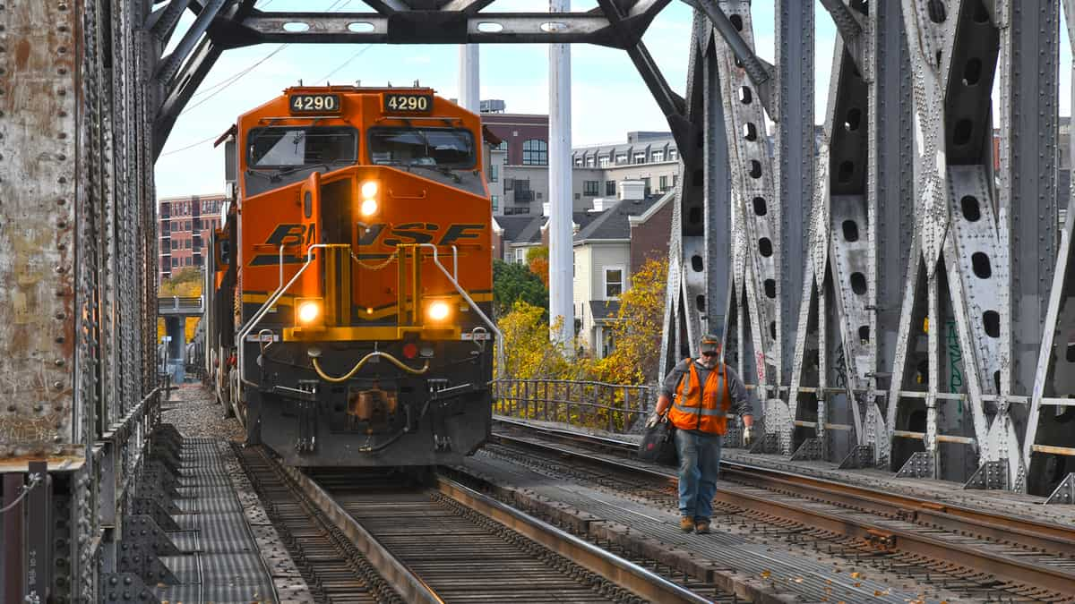 A photograph of a freight train passing through a railroad bridge. A railroad worker is standing next to the train.