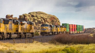 Two locomotives face each other on opposite tracks. One locomotive is hauling intermodal containers behind it.