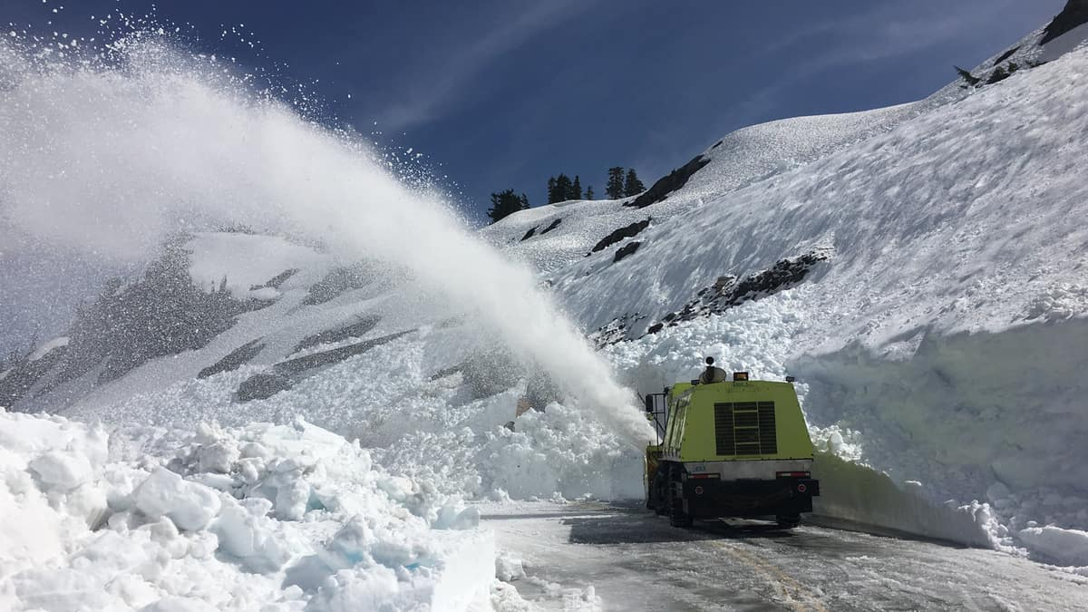 Truck plowing heaps of snow off a highway in Washington state.