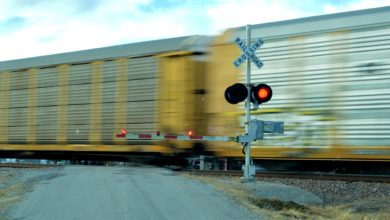 A photograph of railcars passing through a railroad crossing. A railroad crossing sign is in front of the railcars and is signaling that the intersection can't be crossed by vehicular traffic.