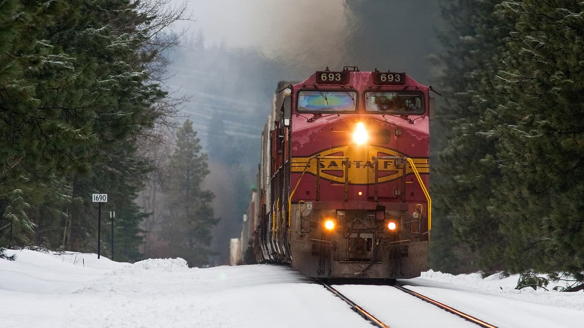 A photograph of a train with a headlight on. There is snow on the ground.