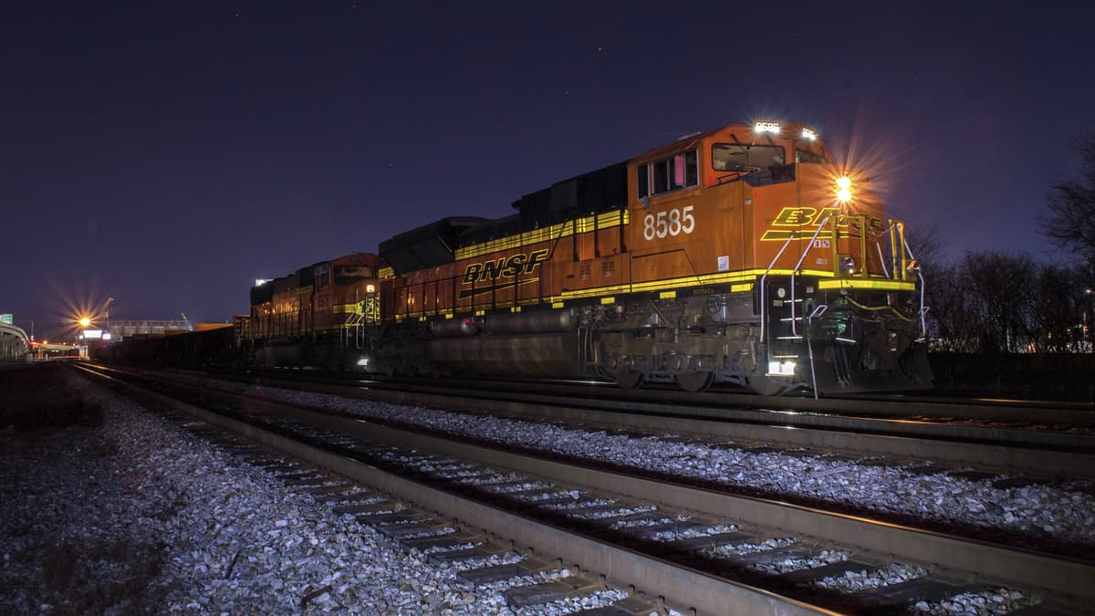 A photograph of a train on a rail track at nighttime.
