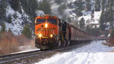 A photograph of a train traveling on rail track. There is snow on the ground.