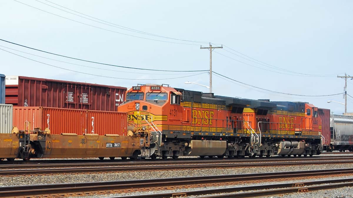 A photograph of a locomotive on a railway track. Intermodal containers are surrounding the locomotive.