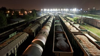 A photograph of a rail yard at night. Inside the rail yard are eight long rows of parked railcars.