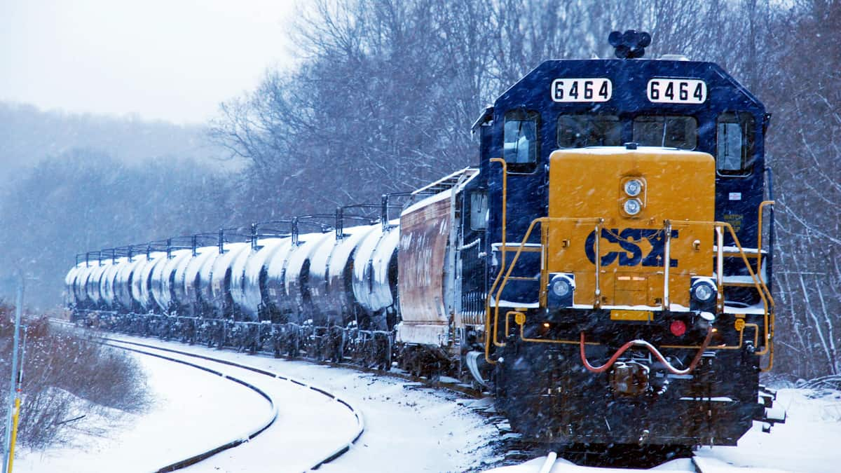 A photograph of a train hauling tank cars in winter. There is snow on the ground.