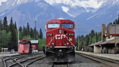 A photograph of a train with tall mountains in the background.