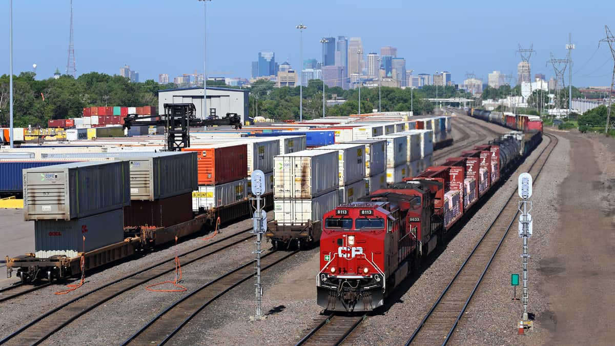 A photograph of a train in a rail yard. Intermodal containers are at the rail yard, sitting nearby.