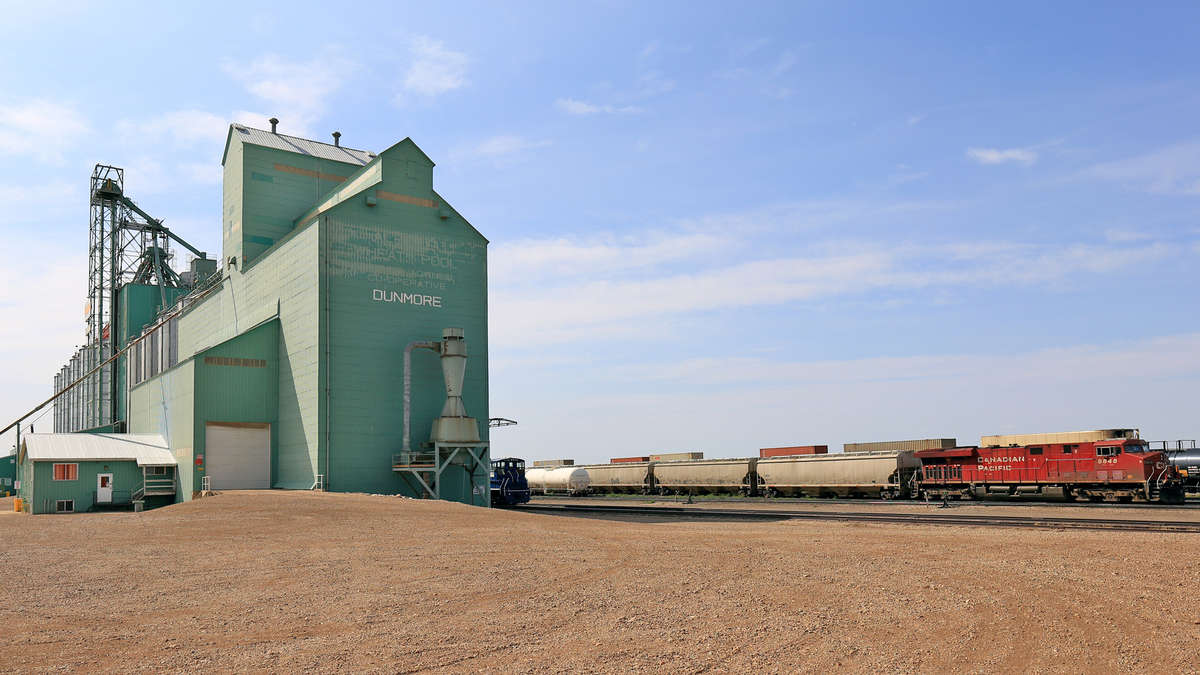 A photograph of a train in a field where grain is harvested. The train is next to a grain elevator.