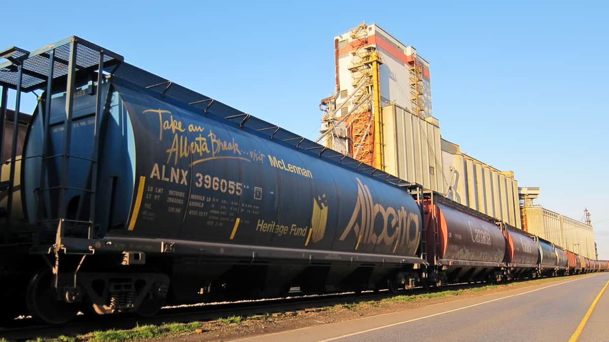 A photograph of a tank car and some railcars at a grain elevator.