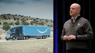 Blue Amazon Prime truck on one side, man speaking to audience on right