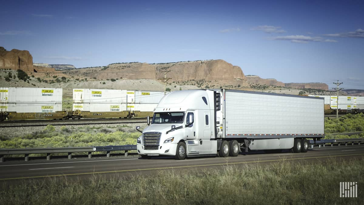 A photograph of a truck. Intermodal containers are behind the truck.
