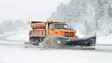 Plow truck clearing a snowy road.