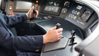A photograph of a person at a driving console.