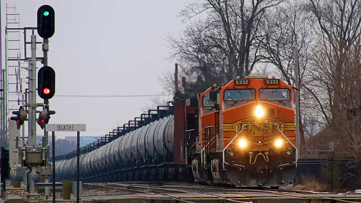 A photograph of a train with its headlights on. The day is cloudy. The locomotive is hauling a line of tank cars behind it.