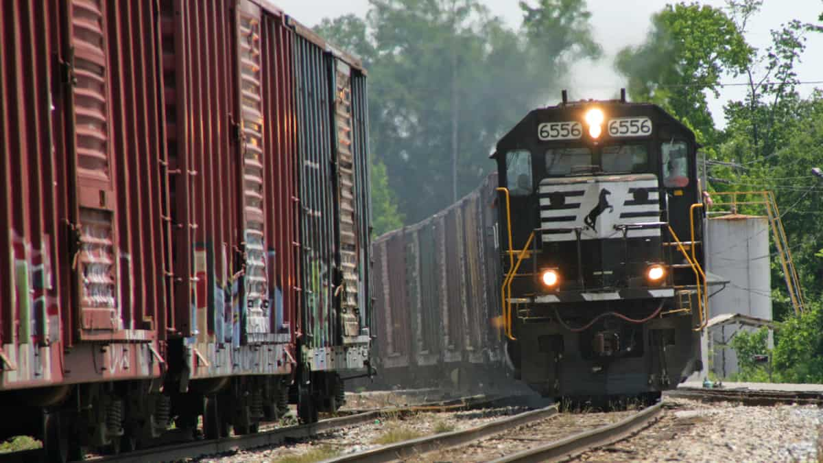 A photograph of a locomotive pulling boxcars. Some parked boxcars are next to the locomotive.