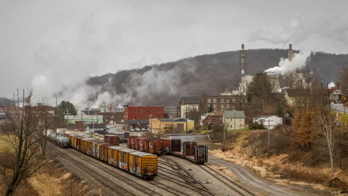 A photograph of boxcars and tank cars parked on rail tracks. The tracks are next to some town buildings. A tree-covered mountain is behind the buildings.