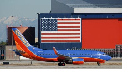 Blue/orange plane beneath a giant American flag.