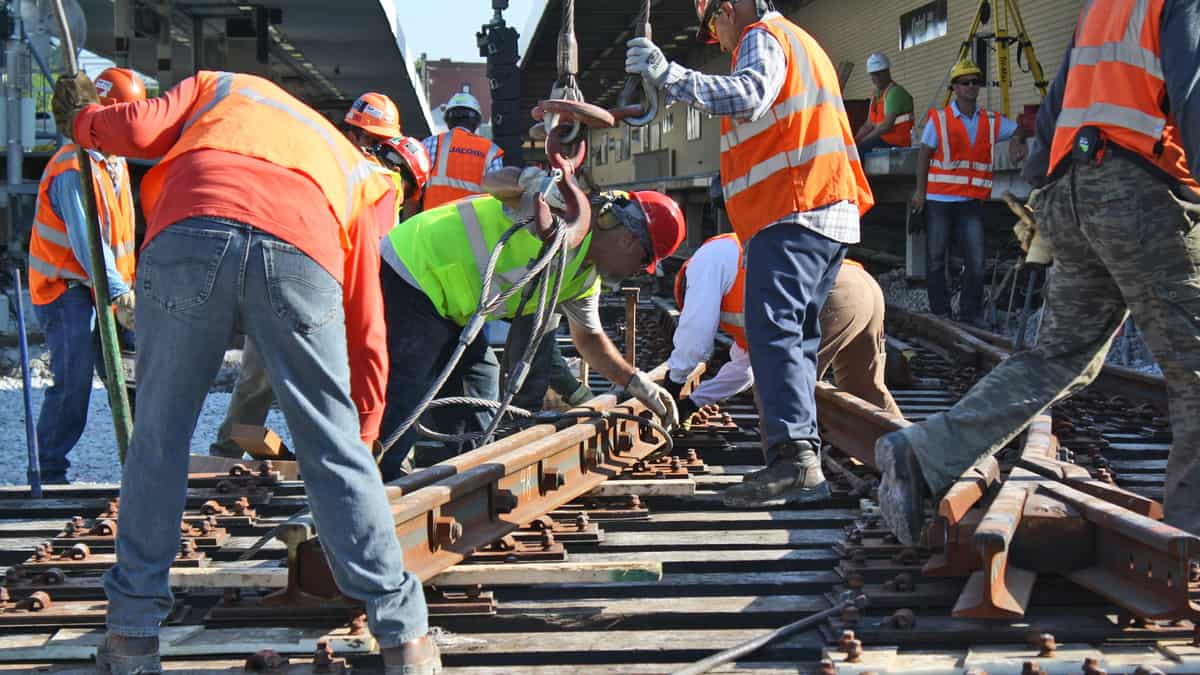 A photograph of railroad employees working on a railroad track.