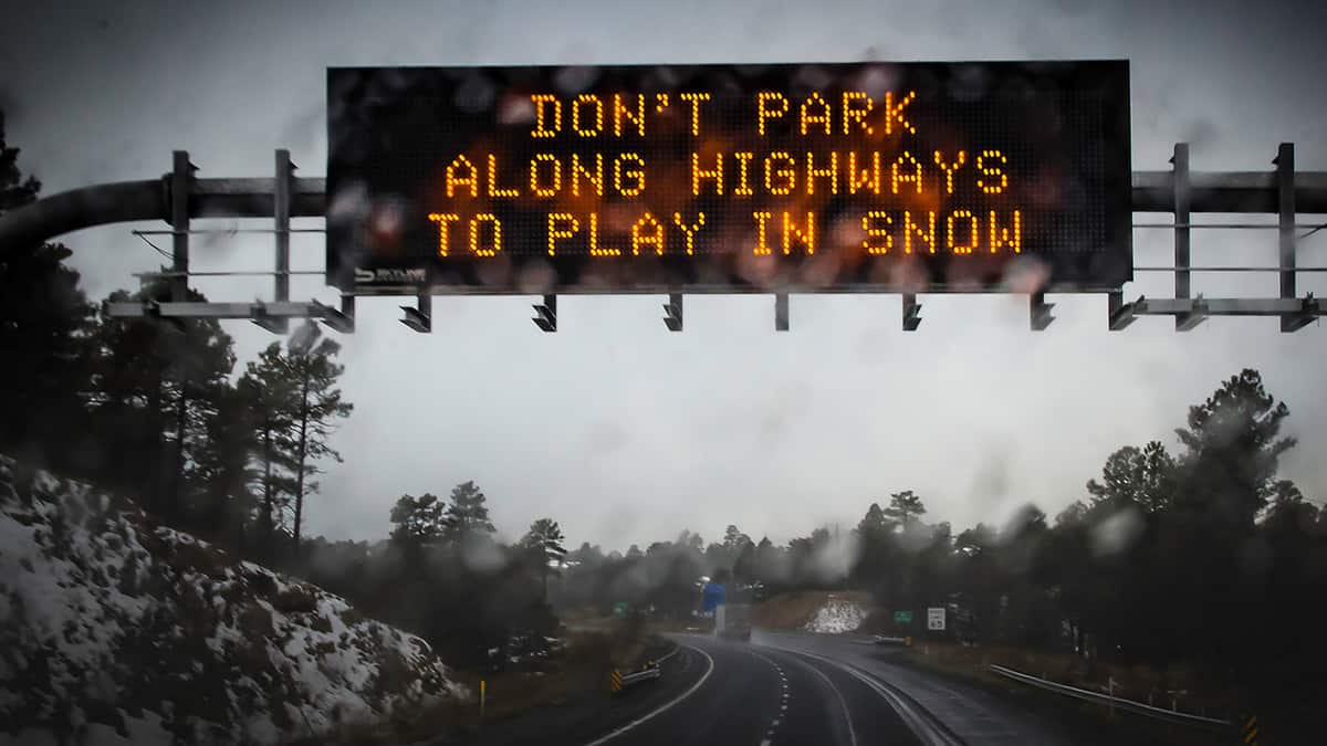 Digital highway sign warning of snowstorm.