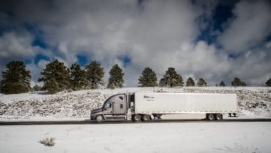 Tractor-trailer moving down a road with snowy hills in the background.
