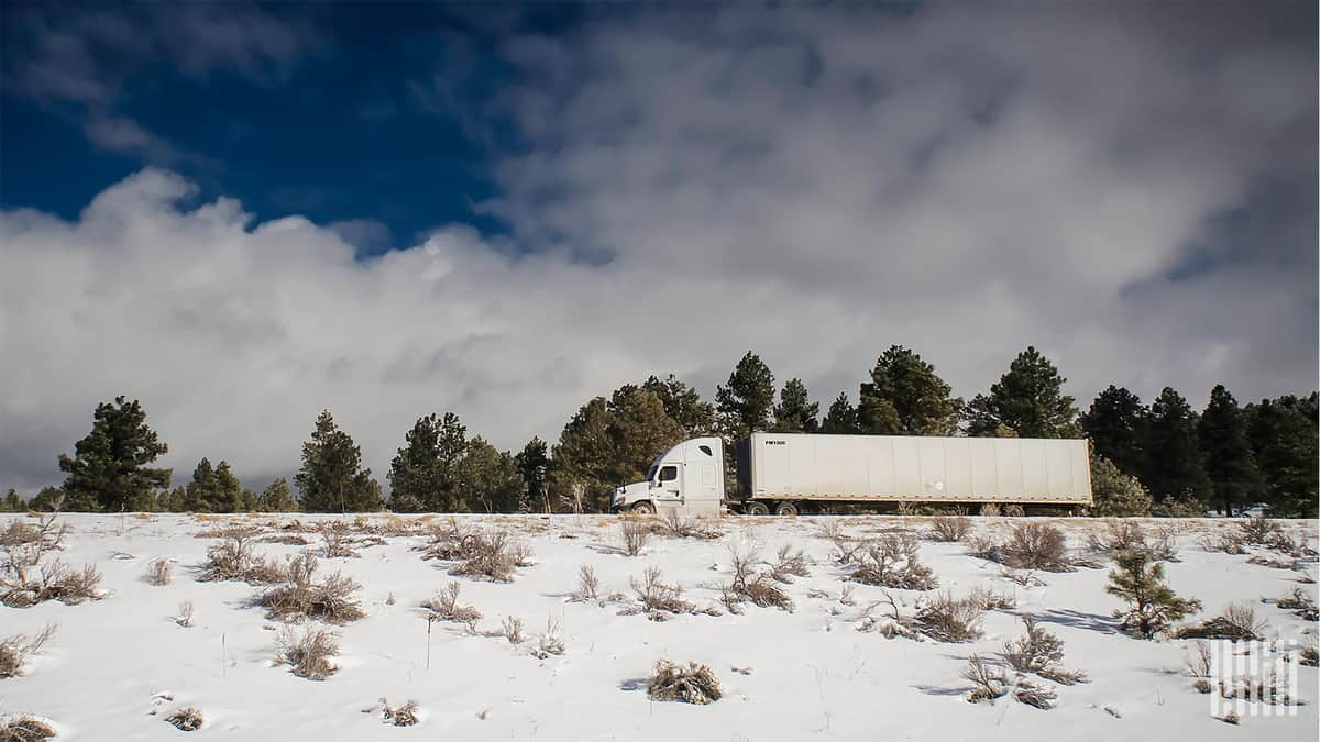 Tractor-trailer moving down snowy road and hillside.