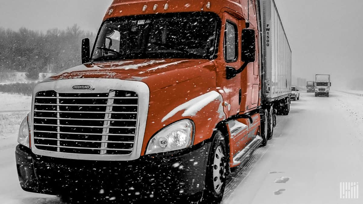 Tractor-trailer parked on side of snowy road.