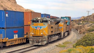 A photograph of a locomotive and intermodal containers.