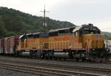 A photograph of a train hauling railcars on a railway track.
