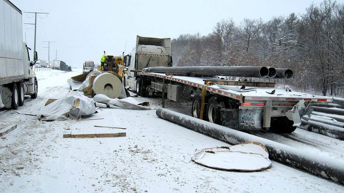 Flatbed truck accident on a snowy Wisconsin road.